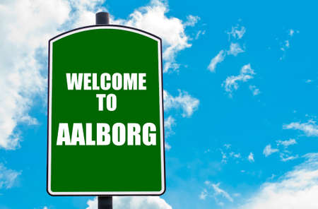 Green road sign with greeting message WELCOME TO AALBORG isolated over clear blue sky background with available copy space. Travel destination concept  image
