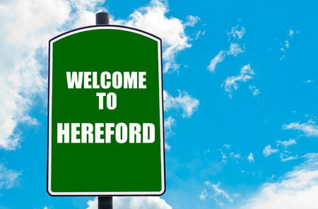 hereford: Green road sign with greeting message WELCOME TO HEREFORD, ENGLAND isolated over clear blue sky background with available copy space. Travel destination concept  image