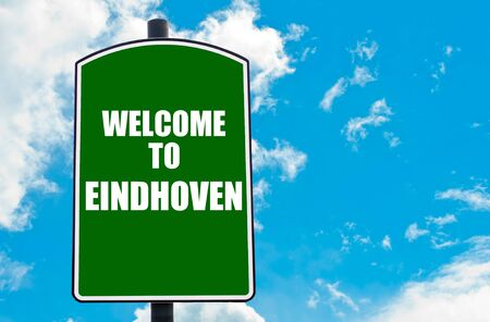 eindhoven: Green road sign with greeting message WELCOME TO EINDHOVEN, NETHERLANDS  isolated over clear blue sky background with available copy space. Travel destination concept  image Stock Photo