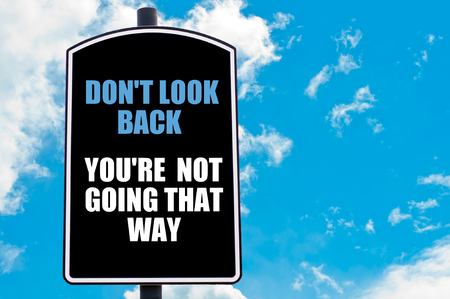 do not: DO NOT LOOK BACK YOU ARE NOT GOING THAT WAY  motivational quote written on road sign isolated over clear blue sky background