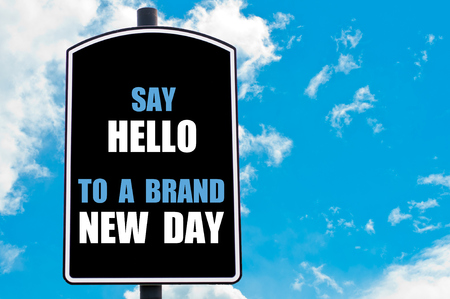 new day: SAY HELLO TO A BRAND NEW DAY motivational quote written on road sign isolated over clear blue sky background