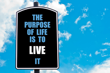 THE PURPOSE OF LIFE IS TO LIVE IT motivational quote written on road sign isolated over clear blue sky background photo