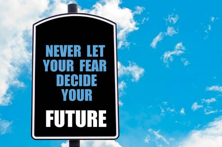 decide: NEVER LET YOUR FEAR DECIDE YOUR FUTURE motivational quote written on road sign isolated over clear blue sky background