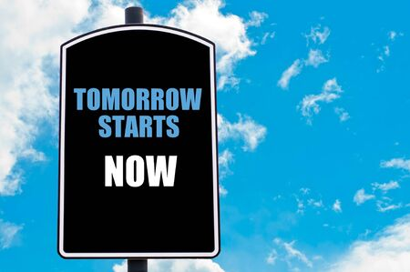 tomorrow: TOMORROW STARTS NOW motivational quote written on road sign isolated over clear blue sky background