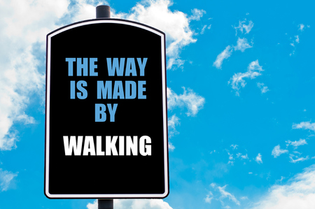 THE WAY IS MADE BY WALKING  motivational quote written on road sign isolated over clear blue sky background photo