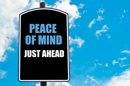 mind: PEACE OF MIND JUST AHEAD  motivational quote written on road sign isolated over clear blue sky background
