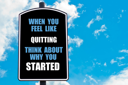 about you: WHEN YOU FEEL LIKE QUITTING THINK ABOUT WHY YOU STARTED  motivational quote written on road sign isolated over clear blue sky background