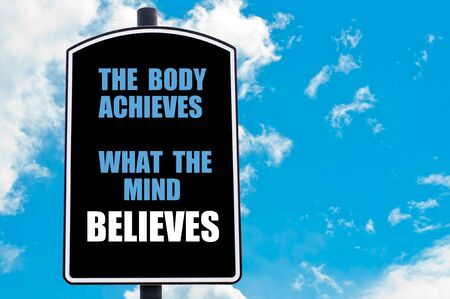 achieves: THE BODY ACHIEVES WHAT THE MIND BELIEVES  motivational quote written on road sign isolated over clear blue sky background