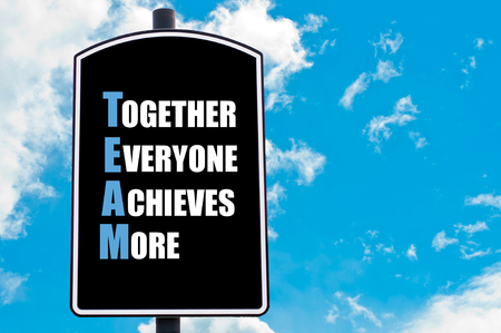 achieves: TEAM as TOGETHER EVERYONE ACHIEVES MORE written on road sign isolated over clear blue sky background