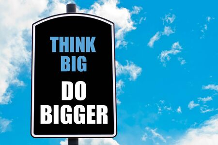 bigger: THINK BIG DO BIGGER  motivational quote written on road sign isolated over clear blue sky background