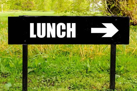 right path: LUNCH written on directional black metal sign with arrow pointing to the right against natural green  background