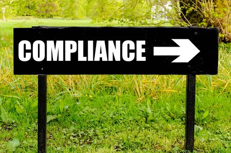 right path: COMPLIANCE written on directional black metal sign with arrow pointing to the right against natural green background
