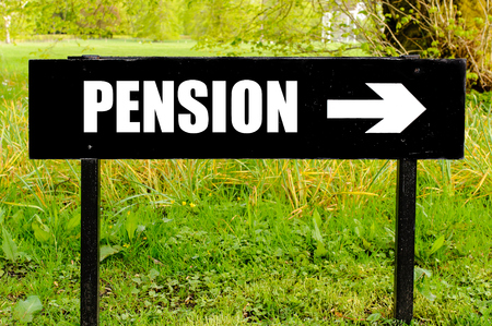 right path: PENSION written on directional black metal sign with arrow pointing to the right against natural green background
