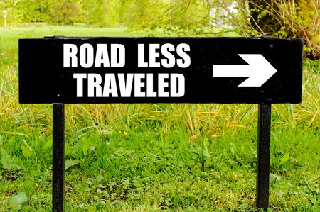 traveled: ROAD LESS TRAVELED written on directional black metal sign with arrow pointing to the right against natural green background