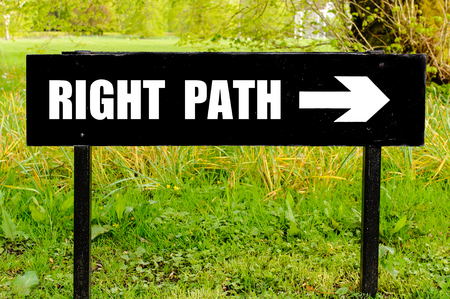 right path: RIGHT PATH written on directional black metal sign with arrow pointing to the right against natural green background