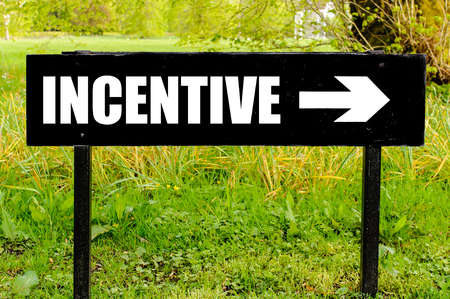 INCENTIVE written on directional black metal sign with arrow pointing to the right against natural green background