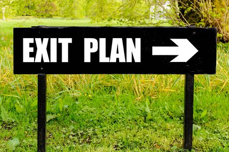 right path: EXIT PLAN written on directional black metal sign with arrow pointing to the right against natural green background