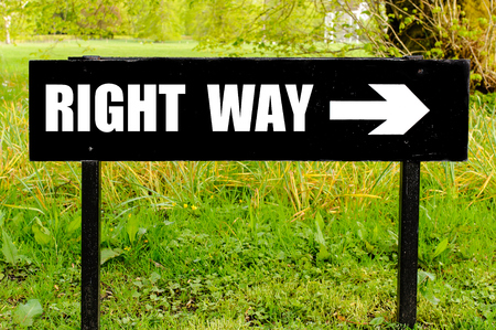 right of way: RIGHT WAY written on directional black metal sign with arrow pointing to the right against natural green background
