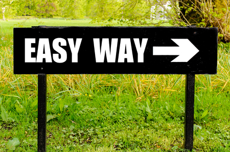 easy way: EASY WAY  written on directional black metal sign with arrow pointing to the right against natural green background Stock Photo