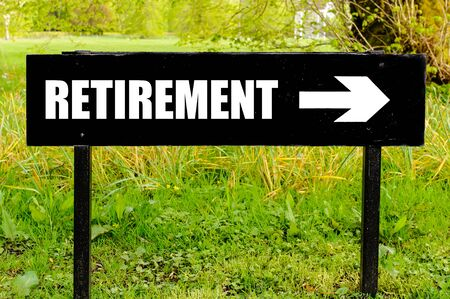 right path: RETIREMENT written on directional black metal sign with arrow pointing to the right against natural green background