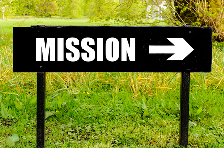 right path: MISSION written on directional black metal sign with arrow pointing to the right against natural green background Stock Photo