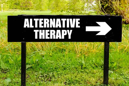 ALTERNATIVE THERAPY written on directional black metal sign with arrow pointing to the right against natural green background Stock Photo