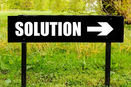 right path: SOLUTION written on directional black metal sign with arrow pointing to the right against natural green background