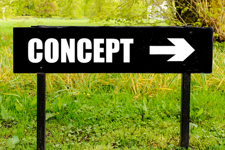 right path: CONCEPT written on directional black metal sign with arrow pointing to the right against natural green background
