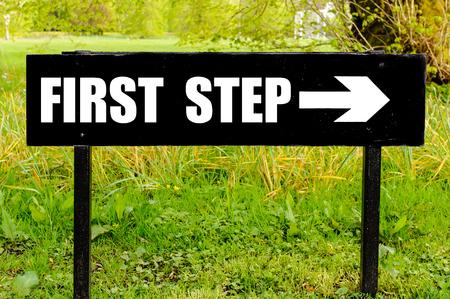 自然緑の背景に対して右を指す矢印と黒い金属の標識に書かれた最初のステップ 写真素材