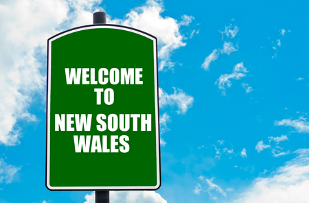 south space: Green road sign with greeting message Welcome to NEW SOUTH WALES isolated over clear blue sky background with available copy space. Travel destination concept  image