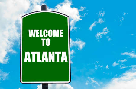 atlanta tourism: Green road sign with greeting message Welcome to ATLANTA isolated over clear blue sky background with available copy space. Travel destination concept  image Stock Photo