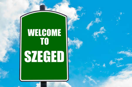 szeged: Green road sign with greeting message Welcome to SZEGED isolated over clear blue sky background with available copy space. Travel destination concept  image