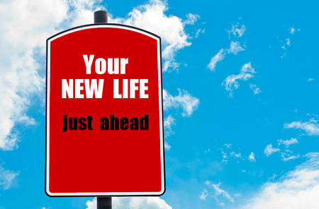 Your New Life Just Ahead motivational quote written on red road sign isolated over clear blue sky background. Concept  image with available copy space Stock Photo