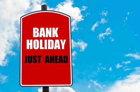 Bank Holiday Net Ahead motievendiecitaat geschreven op rode verkeersbord geïsoleerd over heldere blauwe hemel achtergrond. Concept beeld met beschikbare kopie ruimte