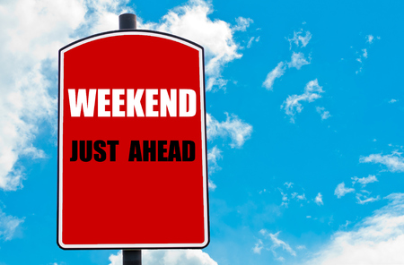 just ahead: Weekend Just Ahead motivational quote written on red road sign isolated over clear blue sky background. Concept  image with available copy space