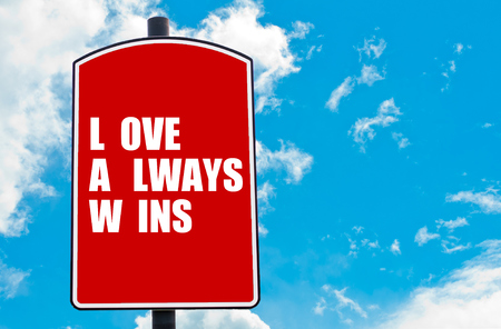 highway love: Love Always Wins motivational quote written on red road sign isolated over clear blue sky background. Concept  image with available copy space