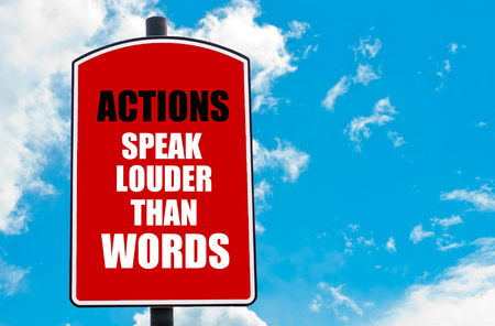 louder: Actions Speak Louder Than Words motivational quote written on red road sign isolated over clear blue sky background. Concept  image with available copy space