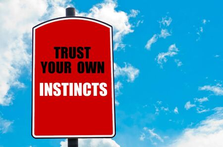 instincts: Trust Your Own Instincts motivational quote written on red road sign isolated over clear blue sky background. Concept  image with available copy space