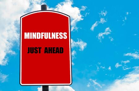just ahead: Mindfulness Just Ahead motivational quote written on red road sign isolated over clear blue sky background. Concept  image with available copy space