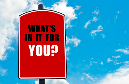 what's ahead: What Is In It For You? motivational quote written on red road sign isolated over clear blue sky background. Concept  image with available copy space