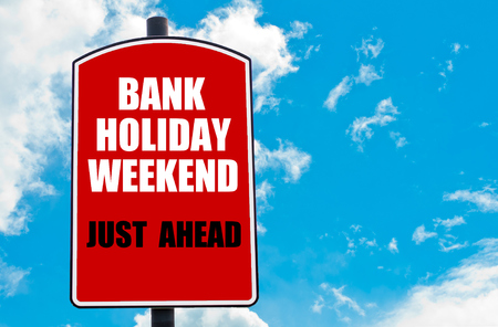 just ahead: Bank Holiday Weekend Just Ahead motivational quote written on red road sign isolated over clear blue sky background. Concept  image with available copy space