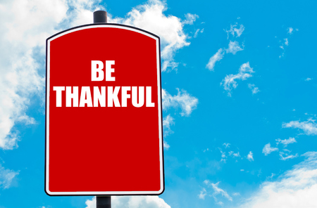 Be Thankful motivational quote written on red road sign isolated over clear blue sky background. Concept  image with available copy space