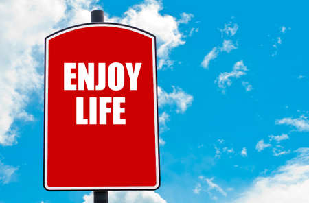 enjoy space: Enjoy Life motivational quote written on red road sign isolated over clear blue sky background. Concept  image with available copy space Stock Photo