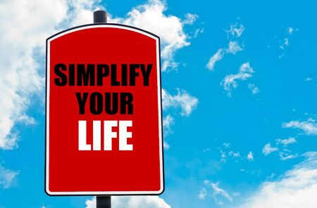 simplify: Simplify Your Life  motivational quote written on red road sign isolated over clear blue sky background. Concept  image with available copy space