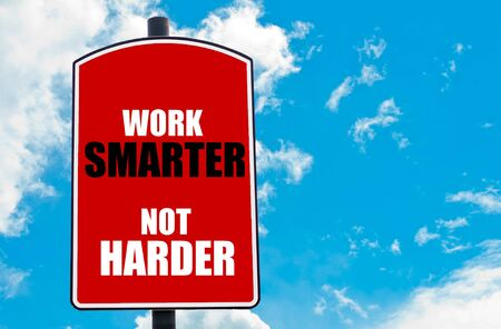 harder: Work Smarter Not Harder  motivational quote written on red road sign isolated over clear blue sky background. Concept  image with available copy space
