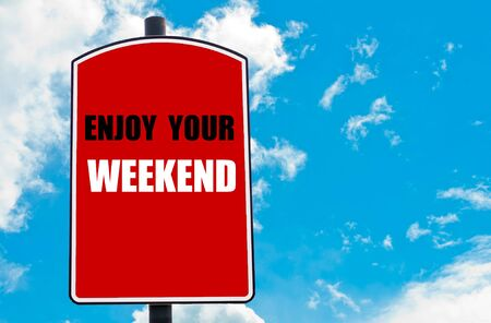 enjoy space: Enjoy Your Weekend  motivational quote written on red road sign isolated over clear blue sky background. Concept  image with available copy space