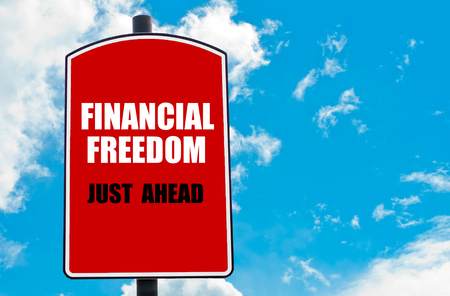 just ahead: Financial Freedom Just Ahead motivational quote written on red road sign isolated over clear blue sky background. Concept  image with available copy space Stock Photo