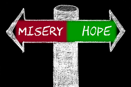 misery: Opposite arrows with Misery versus Hope. Hand drawing with chalk on blackboard