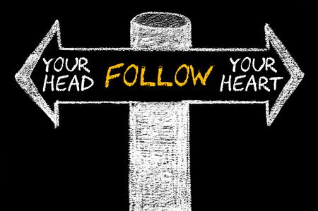 矢印と反対の頭またはあなたの心に従ってください。 黒板にチョークで手書き