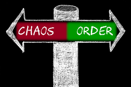 chaos order: Opposite arrows with Chaos versus Order. Hand drawing with chalk on blackboard